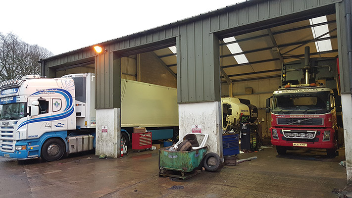 The modern workshop features three bays for commercial vehicles and two for cars)